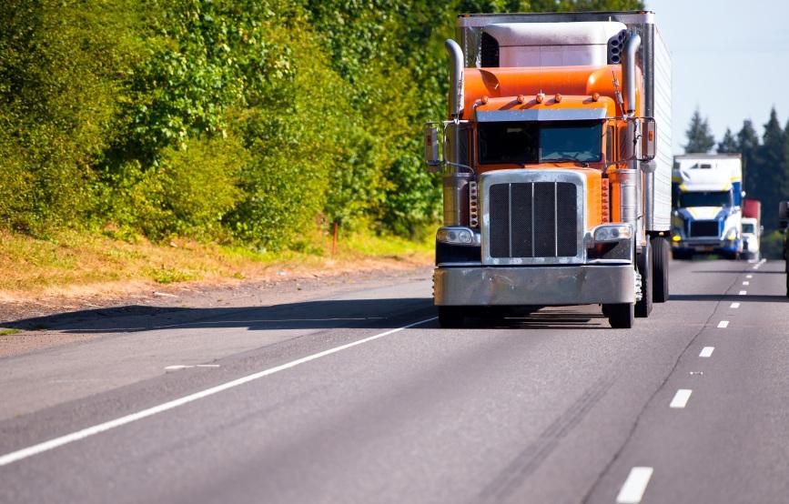 Classic orange semi truck reefer trailer on high way